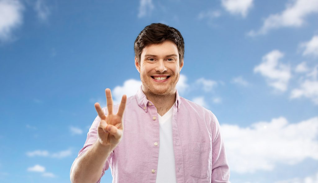 count and people concept - smiling young man showing three fingers over blue sky and clouds background