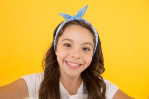 Smile like a model. Adorable small child with happy smile on yellow background. Happy little girl with healthy white smile on cheerful face. Enjoy brighter smile and whiter teeth.