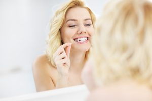 A picture of a young happy woman using dental floss in the bathroom