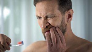 Caucasian man brushing teeth and seeing blood on toothbrush, dental care, ache