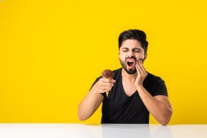 Indian young man eating ice cream in cone and having teeth ache because of cavity, sitting at table against yellow or white background